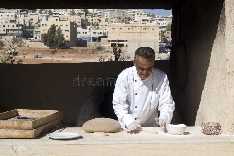 Boulanger jordanien faisant le pain plat à un four extérieur images stock