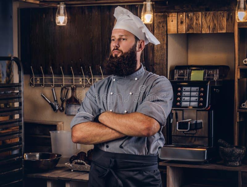Boulanger professionnel dans l'uniforme de cuisinier posant avec les bras croisés près dans la boulangerie image libre de droits