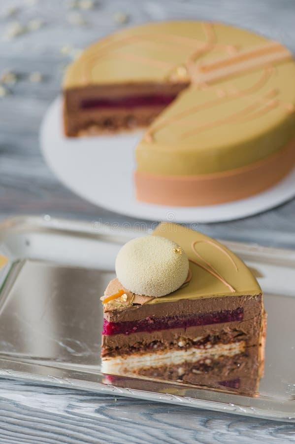Boulangerie avec le morceau de gâteau jaune peu commun de mousse avec le dacquoise d'amande, confit de framboise, couche croustil photo libre de droits