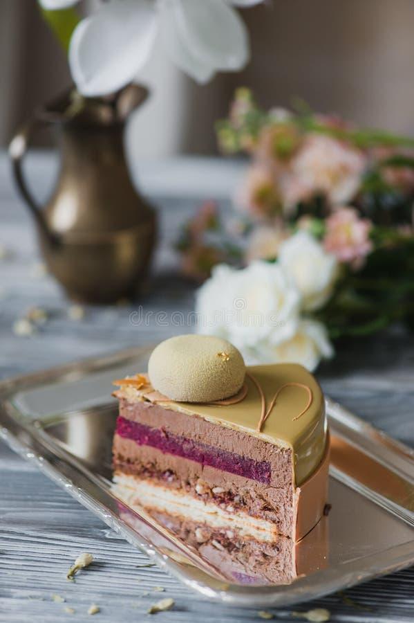 Boulangerie avec le morceau de gâteau jaune peu commun de mousse avec le dacquoise d'amande, confit de framboise, couche croustil image libre de droits