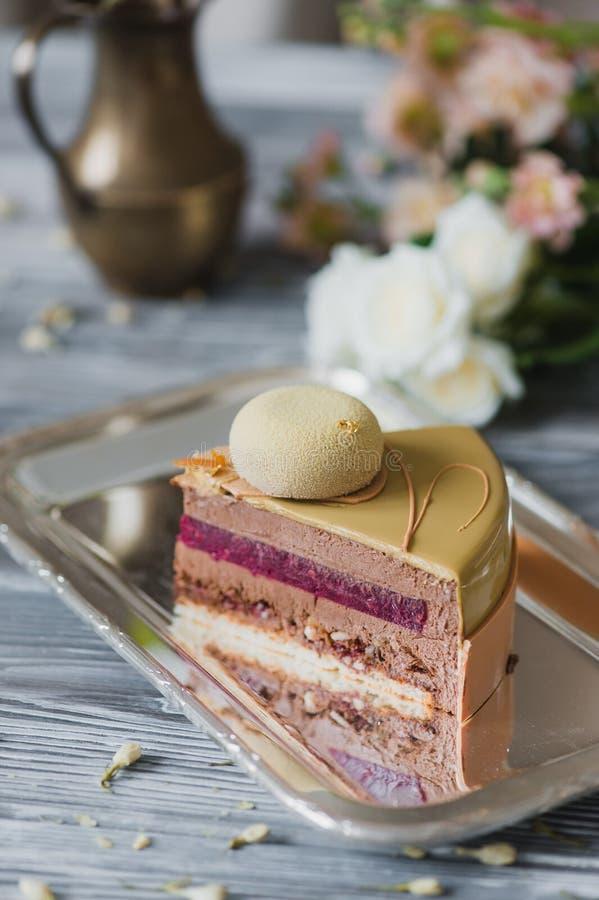 Boulangerie avec le morceau de gâteau jaune peu commun de mousse avec le dacquoise d'amande, confit de framboise, couche croustil photographie stock libre de droits
