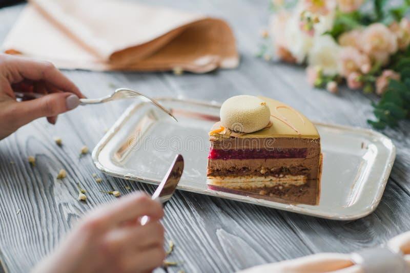 Boulangerie avec le morceau de gâteau jaune peu commun de mousse avec le dacquoise d'amande, confit de framboise, couche croustil images libres de droits