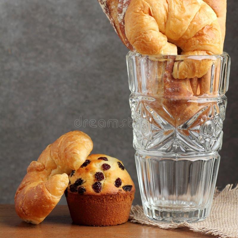 Boulangerie de petit pain de pointe de croissant dans le coup en verre sur la table de teakwood images stock