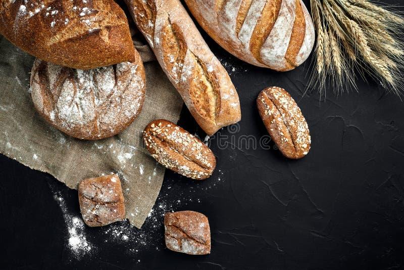 Boulangerie - miches de pain et petits pains croustillants rustiques d'or sur le fond noir de tableau images stock