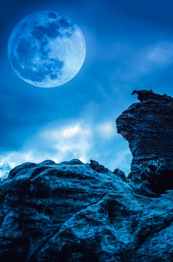 Boulder against blue sky with clouds and beautiful full moon at. Boulder with blue sky background and beautiful full moon behind cloud at night. Outdoor at stock photos