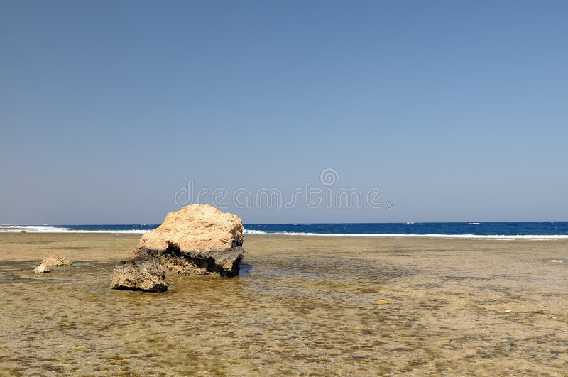 Boulder on deserted beach royalty free stock images