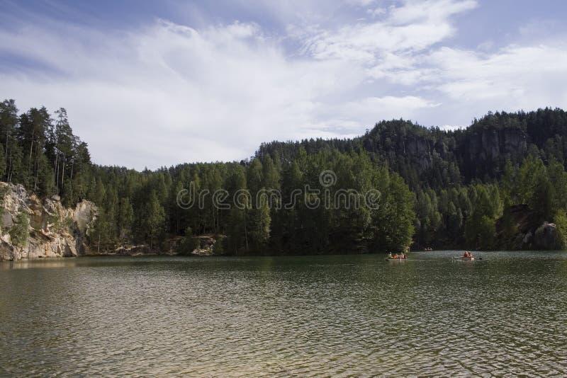 Boulder ed alberi dietro un lago fotografia stock libera da diritti