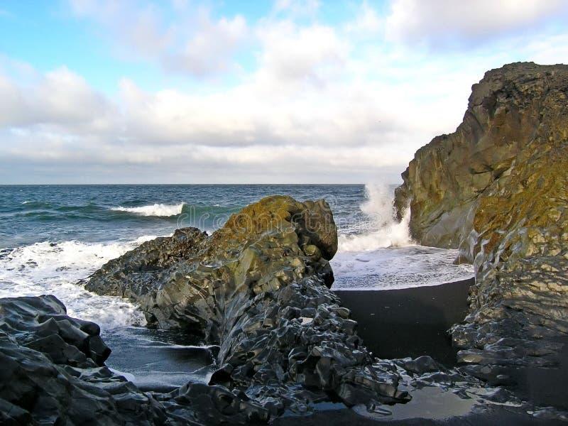 Boulder sulla spiaggia circa cui le onde sono rotte Spruzzo di mare al sole Pietra in alghe fotografia stock