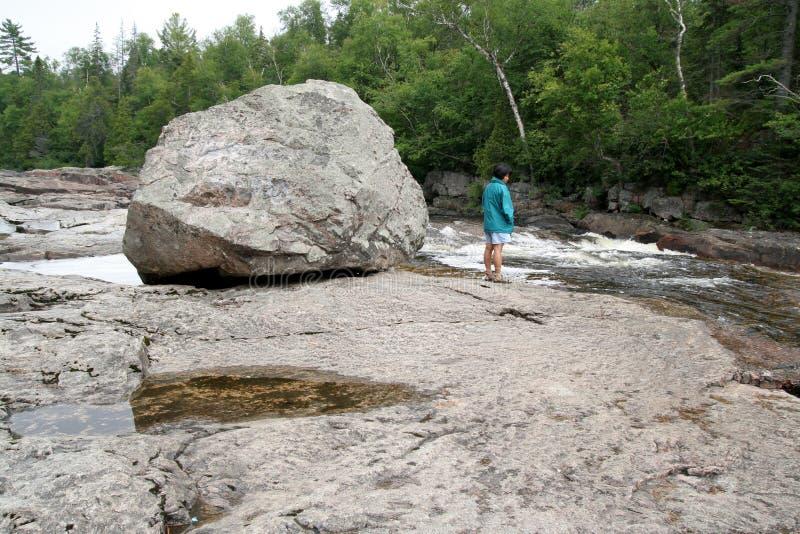 Boulder und Frau auf dem Sand-Fluss stockfoto