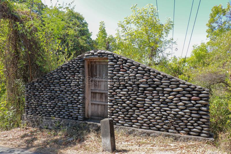 A boulder wall with closed wooden doors. Stone wall by the road in Bali Island, Indonesia. Enter the jungle. Mystical place with m stock image