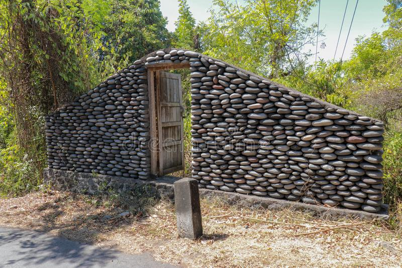 A boulder wall with open wooden doors. Stone wall by the road in Bali Island, Indonesia. Enter the jungle. Mystical place. royalty free stock photo