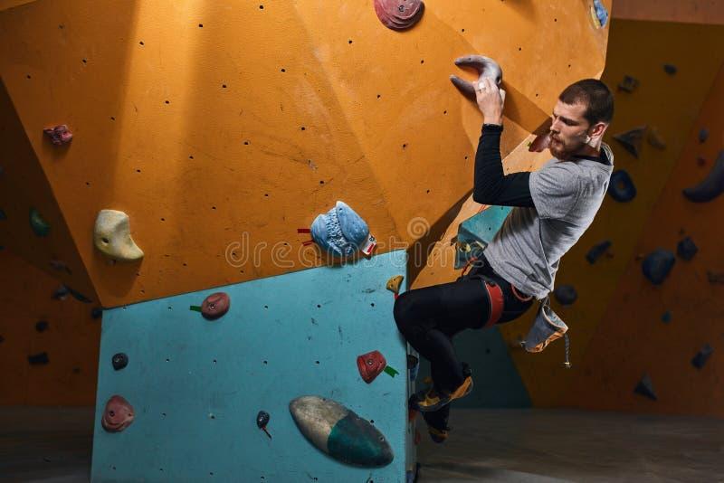 Boulderer atlético considerável que treina duramente em ajustes de escalada internos foto de stock