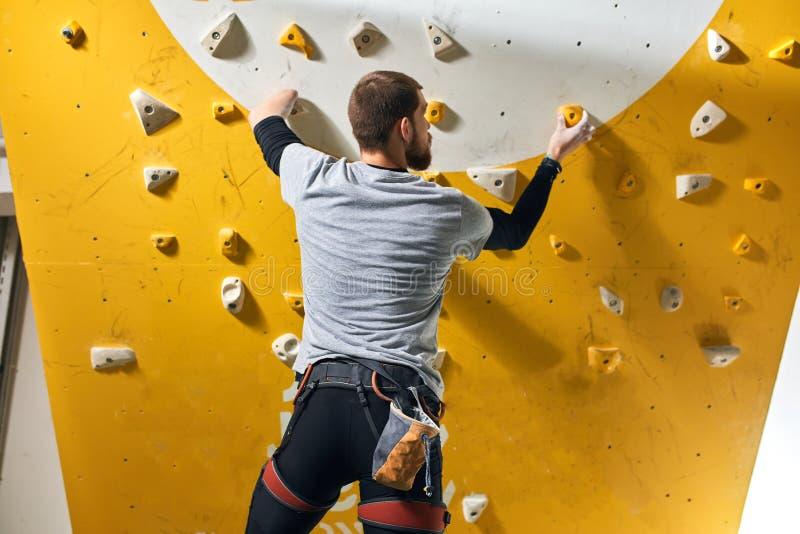 Boulderer pozycja przed żółtą sztuczną ścianą, sprawdza chwyty fotografia stock