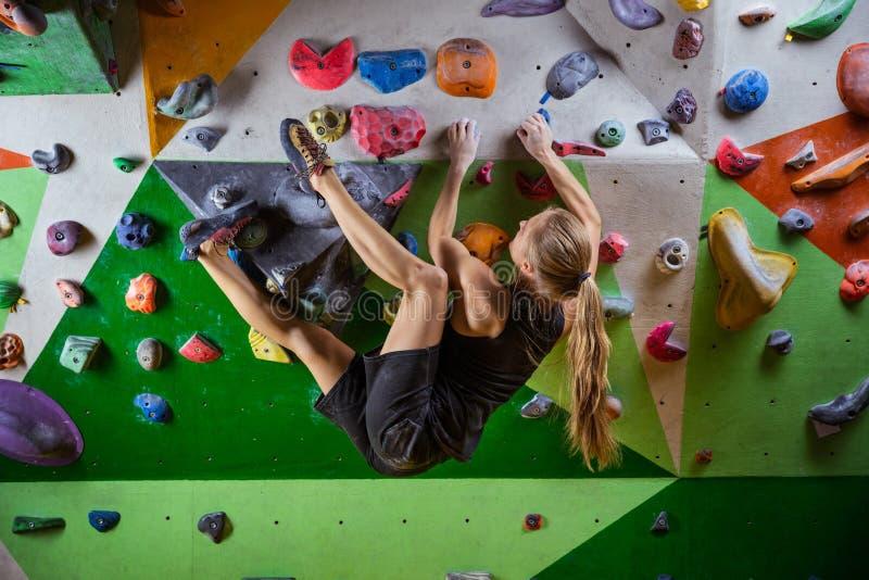 bouldering在上升的健身房的伸出的墙壁上的少妇 免版税库存照片