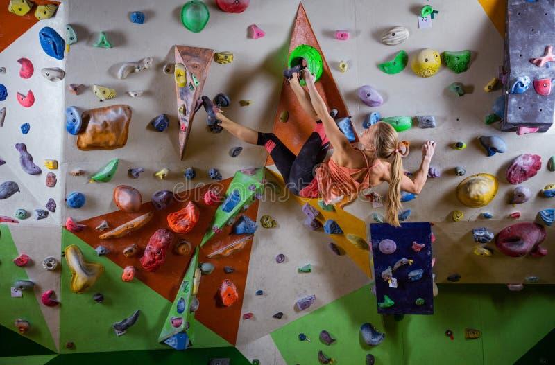 bouldering在上升的健身房的伸出的墙壁上的少妇 库存照片
