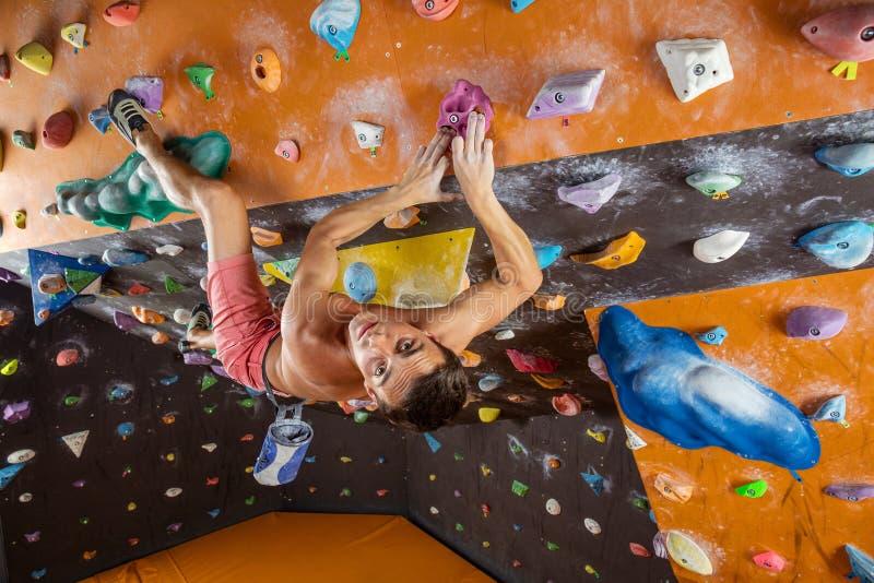 bouldering在室内上升的健身房的年轻人 免版税库存照片