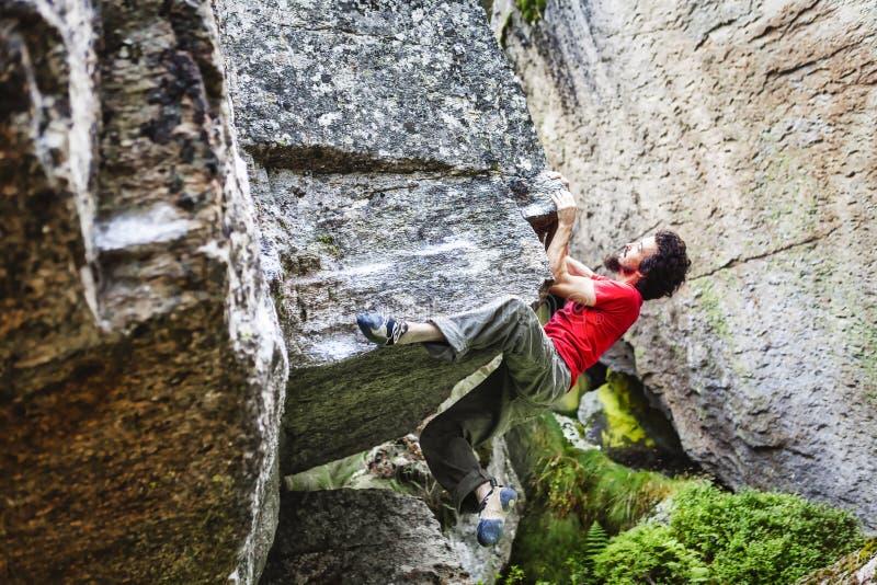 Bouldering del ragazzo all'aperto su una pietra immagini stock
