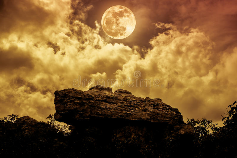 Boulders against sky with clouds and beautiful full moon at nigh royalty free stock images