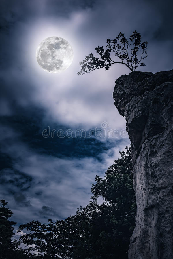 Boulders against sky with cloudy and beautiful full moon. stock image