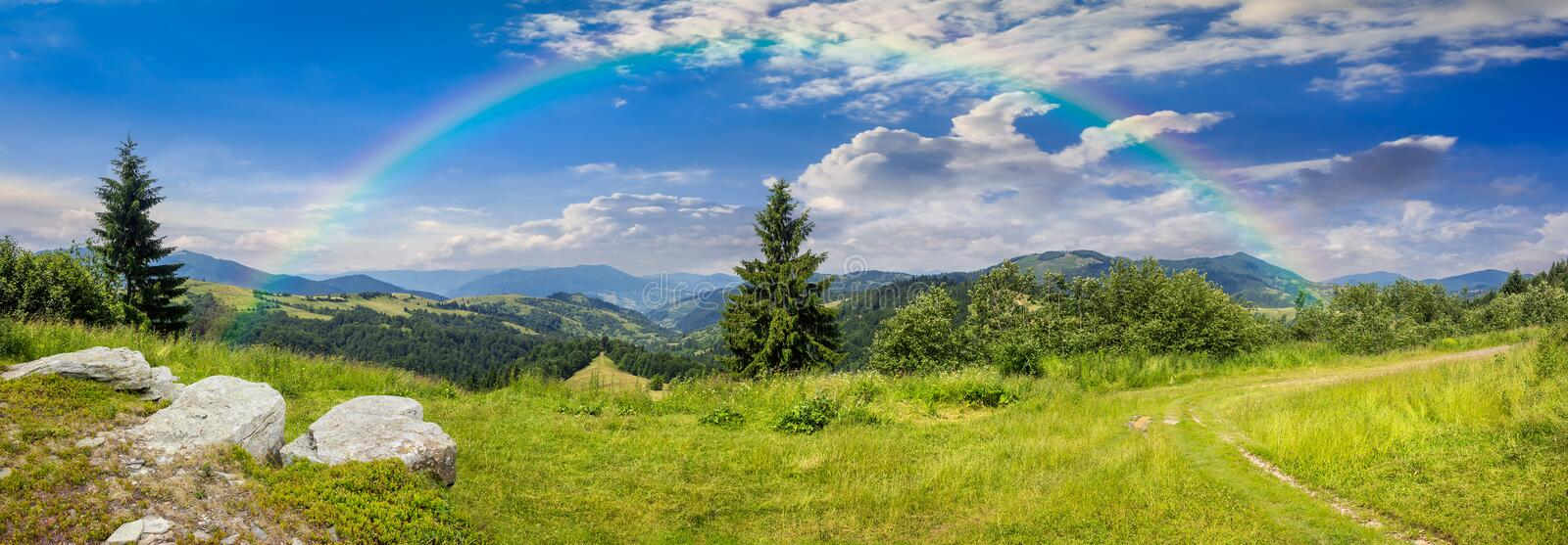 Boulders on hillside meadow in mountain with rainbow. Pnoramic collage landscape. boulders on the meadow with path on the hillside and two pine trees on top of royalty free stock photo