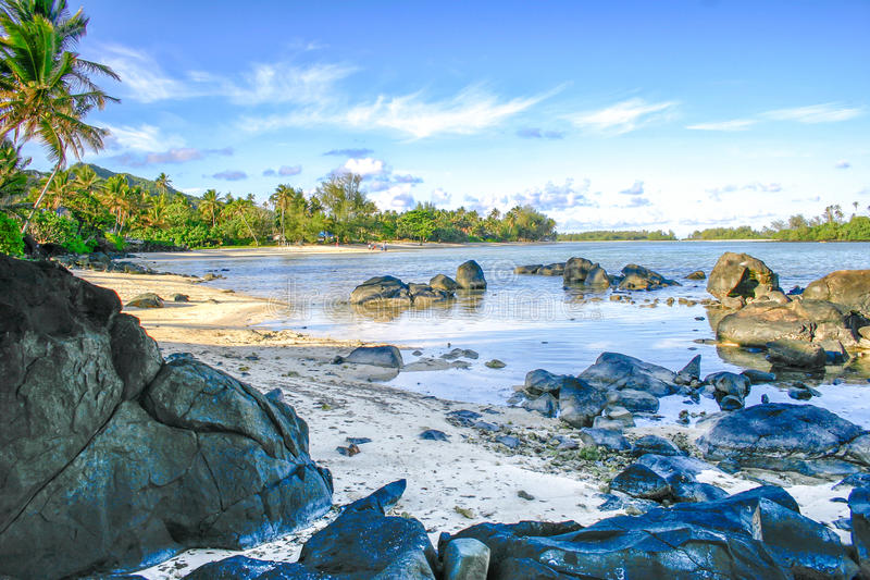 Boulders rest in a crystal clear lagoon on the tropical island of Rarotonga, Cook Islands. royalty free stock image