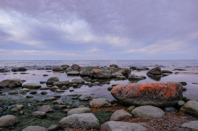 Boulders on a sea shore. Wild rocky seashore on a cloudy day. Fabulous seascape royalty free stock image