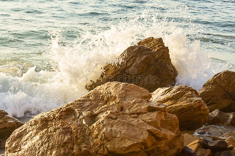 Boulders at shoreline, with ocean wave splash foam royalty free stock photography