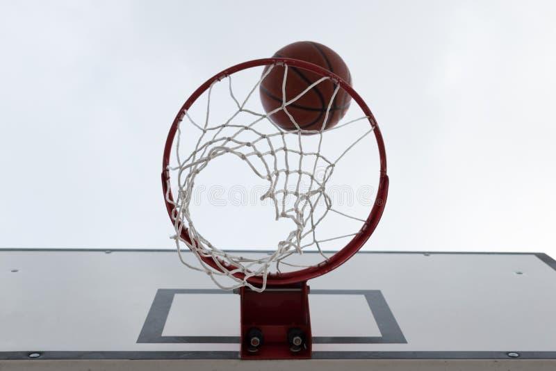 Boule à l'intérieur du cercle de basket-ball rouge, panier contre le ciel blanc Terrain de basket extérieur Conseil blanc images libres de droits