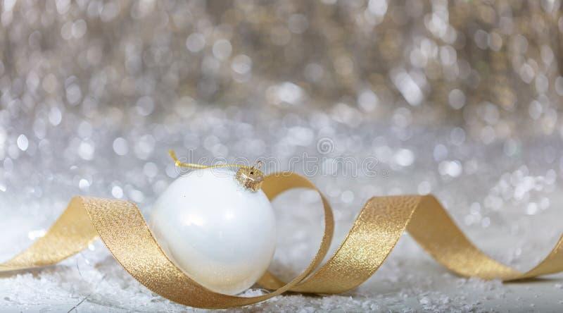 Boule blanche de Noël, ruban d'or et neige, lumières abstraites de bokeh photo stock