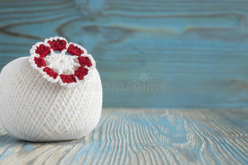 Boule blanche des fils de coton naturels d'eco pour le tricotage, le crochet et la fleur tricotée Fond en bois bleu rustique, irl photos stock