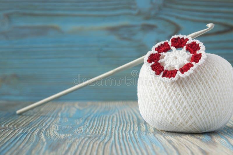 Boule blanche des fils de coton naturels pour le tricotage, le crochet et la fleur et le crochet tricotés Fond en bois bleu rusti photos libres de droits