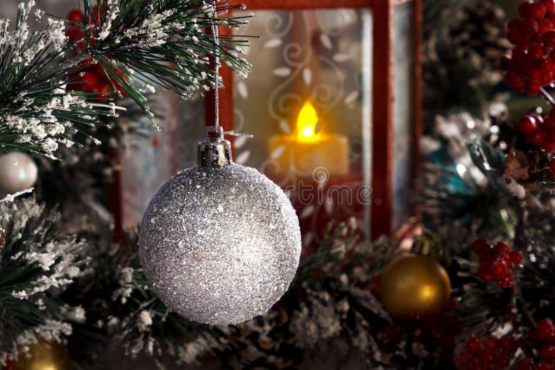 Boule brillante blanche accrochant sur une branche d'un arbre de Noël contre une lanterne rouge avec une bougie photos stock