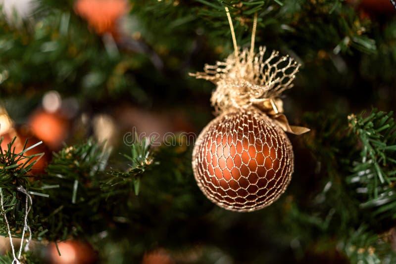 Boule brune de Noël accrochant sur des branches de pin avec le fond de fête photographie stock libre de droits