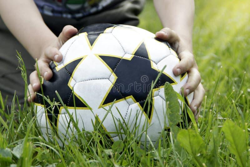 Boule dans les mains sur l'herbe photo stock