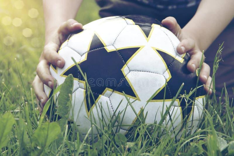 Boule dans les mains sur l'herbe photographie stock libre de droits