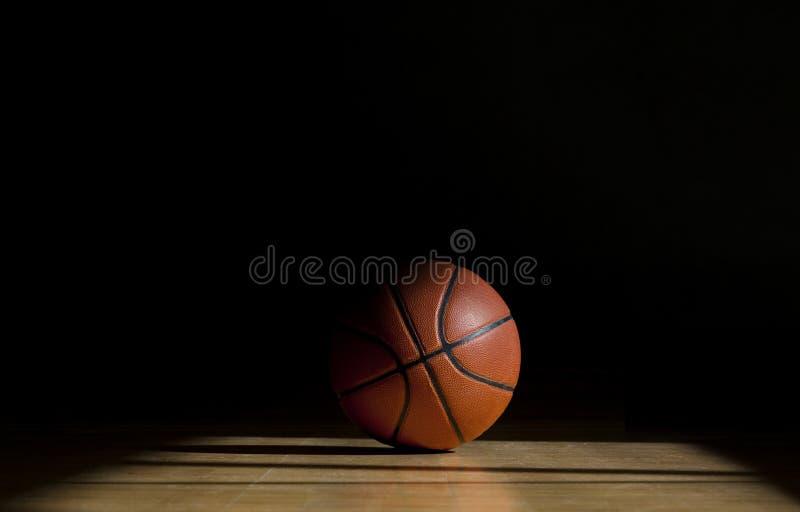 Boule de basket-ball sur le parquet avec le fond noir photos stock