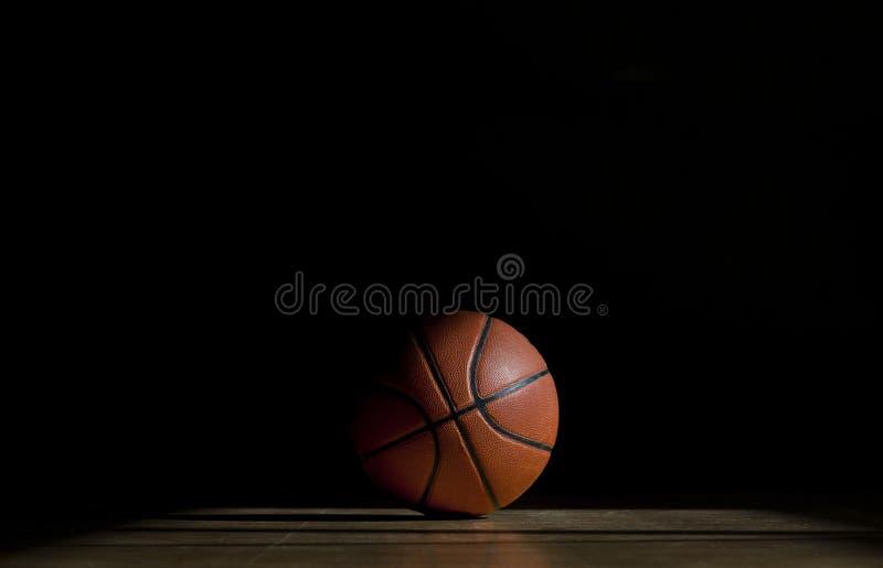 Boule de basket-ball sur le parquet avec le fond noir image libre de droits