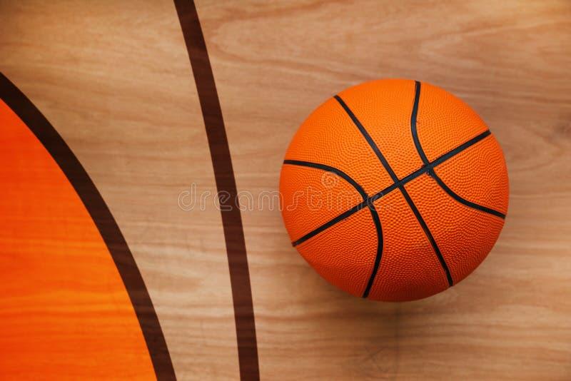 Boule de basket-ball sur le plancher de cour photographie stock