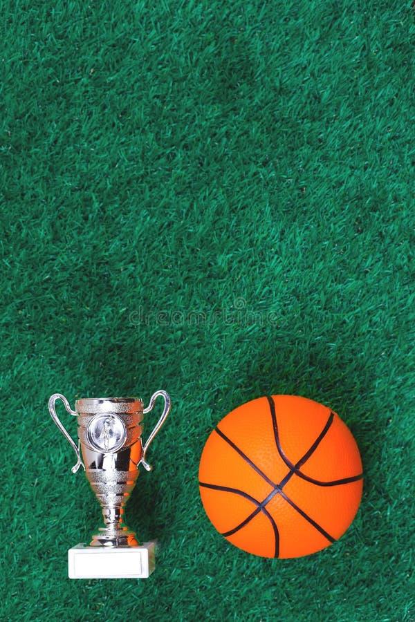 Boule de basket-ball, une tasse contre le gazon artificiel vert photographie stock