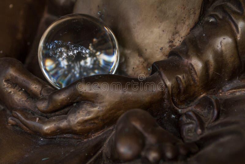 Boule de cristal étonnante dans des mains de statue de moine photographie stock libre de droits