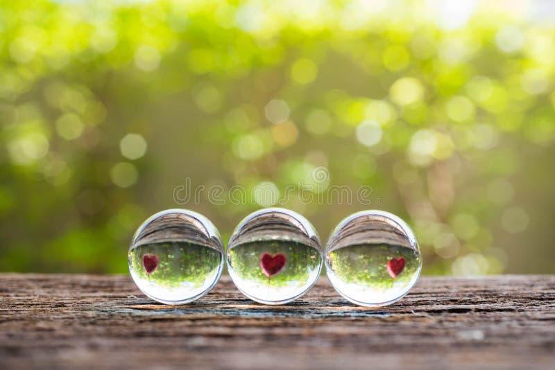 Boule de cristal avec la réflexion du coeur et du bokeh rouges sur le dos en bois photographie stock