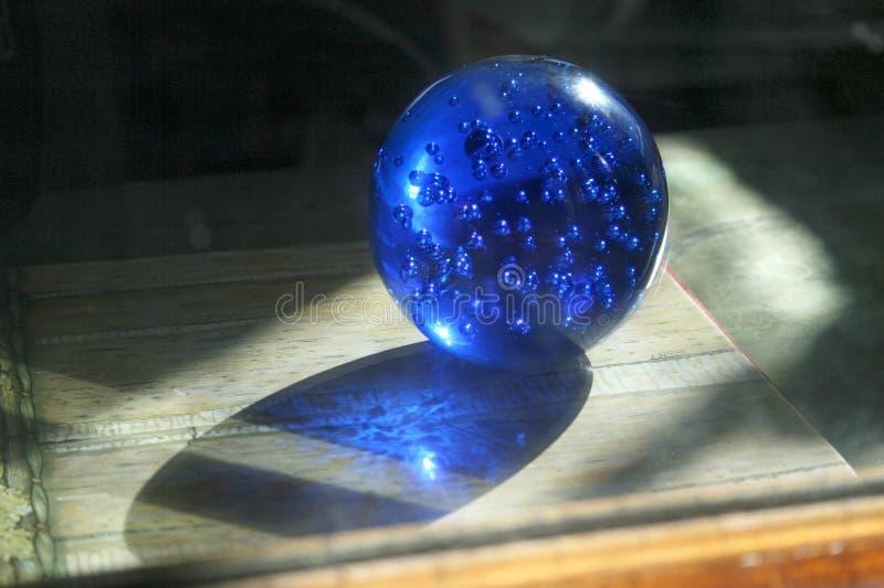 Boule de cristal en verre bleue avec des bulles Sphère magique avec la lumière shing par le globe de boule photo libre de droits