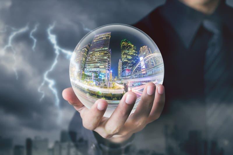 Boule de cristal de prise de main d'homme d'affaires avec la nuit de ville à l'intérieur photo stock