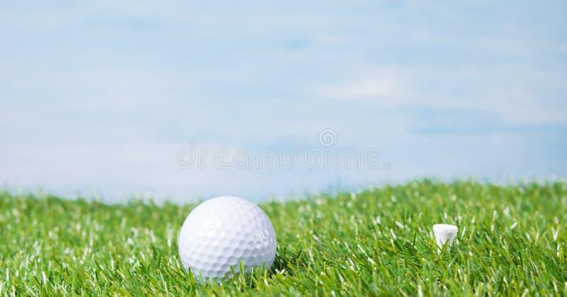 Boule de golf contre le ciel et une pelouse verte photo stock