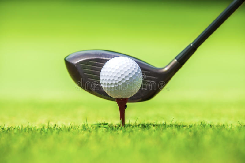 Boule de golf derrière le conducteur au champ d'exercice photo stock