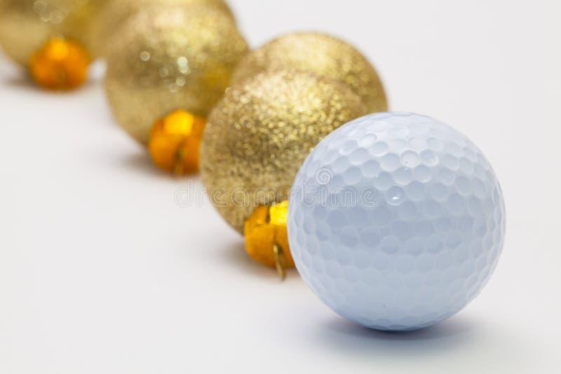 Boule de golf et décoration de Noël sur le bureau blanc photographie stock