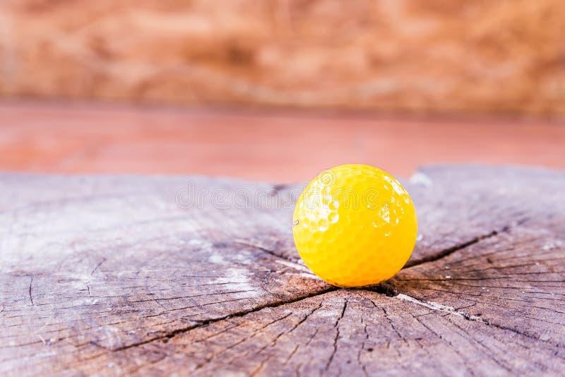 Boule de golf miniature jaune sur le fond blanc image stock