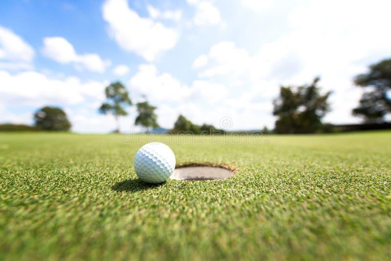 Boule de golf près de trou, photographie stock