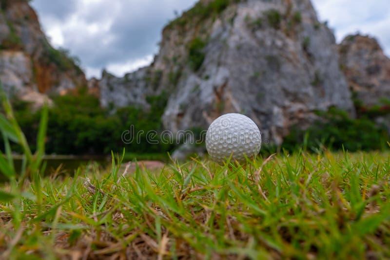 Boule de golf sur l'herbe près de la montagne images libres de droits