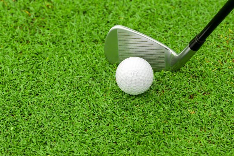 Boule de golf sur la pièce en t devant le conducteur sur le cours vert photos stock
